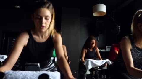 ms mature woman riding stationary bike during cycling class in fitness studio - 30 39 years stock videos & royalty-free footage
