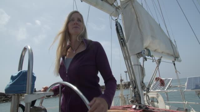 vídeos de stock e filmes b-roll de mature woman sailing her sailboat - 50 54 anos