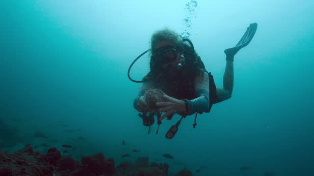 mature woman scuba diver removing fishing net from coral reef - aqualung diving equipment stock videos & royalty-free footage