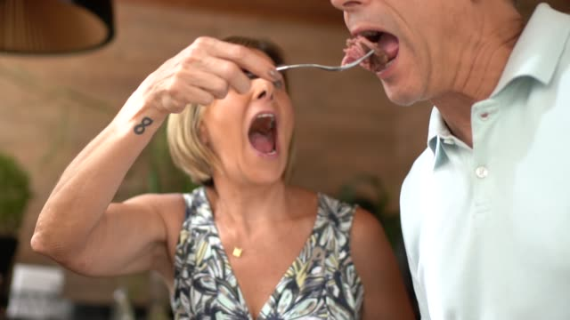 mature woman serving meat to man during barbecue - enjoyment stock videos & royalty-free footage