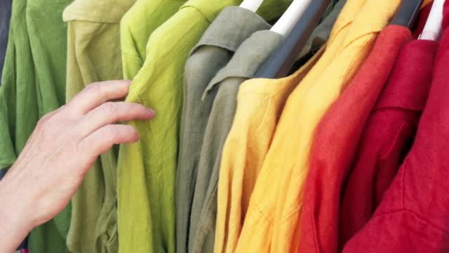 stockvideo's en b-roll-footage met rijpe vrouw winkelen voor kleding - kledingrek