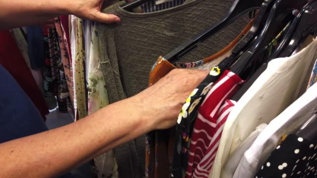 stockvideo's en b-roll-footage met volwassen vrouw winkelen voor kleding - kledingrek