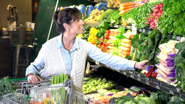 mature woman shopping for groceries in produce section - freschezza video stock e b–roll