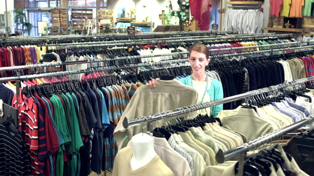 Mature woman shopping for men's shirts in clothing store