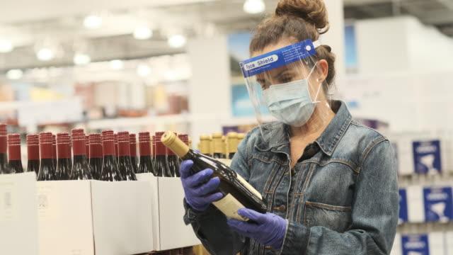 保護フェイスマスク、外科用手袋、フェイスシールドを着用したメガストア通路でワインを買う成熟した女性 - メガストア点の映像素材/bロール