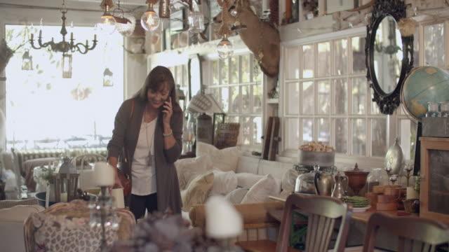 mature woman shopping in an antique store - ギフトショップ点の映像素材/bロール