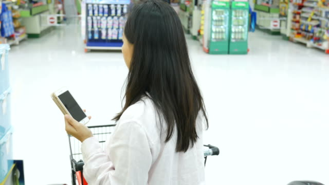 Mature woman shopping in department store, using smart phone on escalator