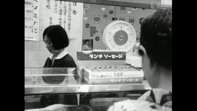 mature woman shops for food in japanese supermarket; 1966 - periodo showa video stock e b–roll