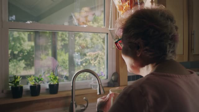 slo mo. mature woman sips her morning cup of coffee and looks out the kitchen window. - terza età video stock e b–roll