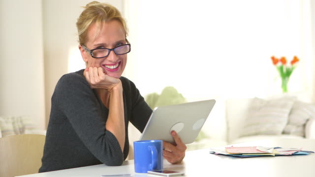 Mature woman sitting at desk with tablet computer