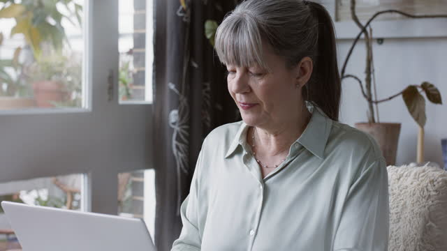 mature woman sitting at home in front of laptop - coffee cup stock videos & royalty-free footage