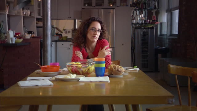 ms mature woman sitting at table in kitchen / jersey city, new jersey, usa - negative emotionen stock-videos und b-roll-filmmaterial