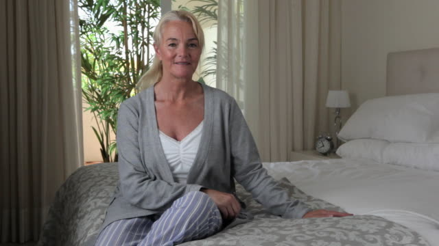 mature woman sitting on bed - double bed stock videos & royalty-free footage