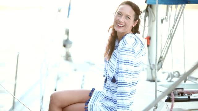 vidéos et rushes de femme mature assise sur le pont du voilier - quadragénaire
