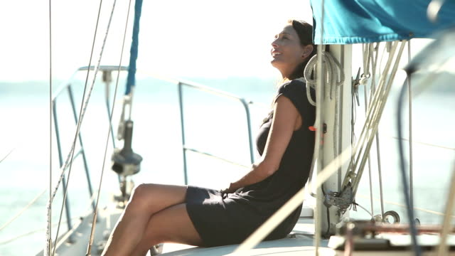 mature woman sitting on deck of sailboat - cross legged stock videos & royalty-free footage