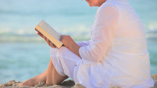 mature woman sitting reading on a beach / cape town, western cape, south africa - one mature woman only stock videos & royalty-free footage