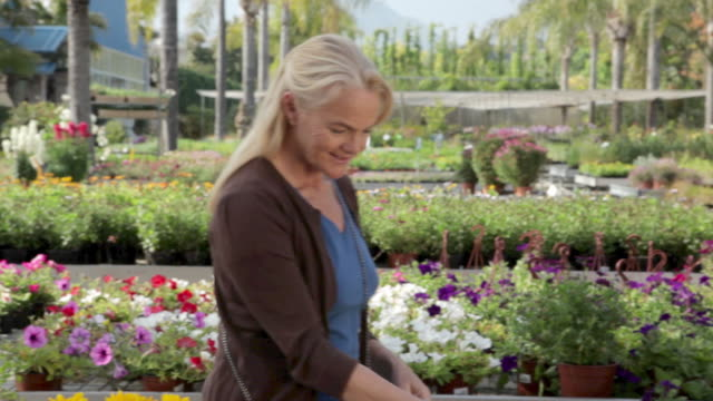 mature woman smelling flowers in garden centre - only mature women stock videos & royalty-free footage
