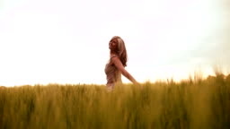 Mature woman spinning happily in wheat field