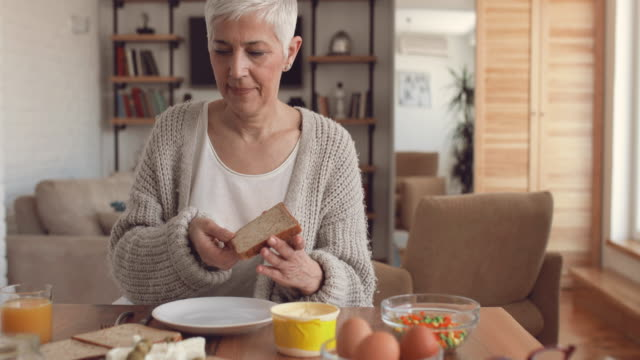 vídeos y material grabado en eventos de stock de mujer madura extendiendo la mantequilla sobre una rebanada de pan teniendo un desayuno en casa. - mantequilla