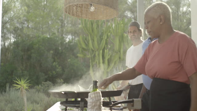 a mature woman stirs a paella pan - mature couple stock videos & royalty-free footage