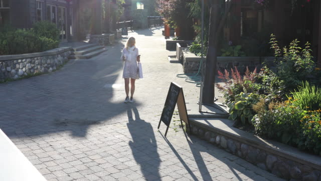mature woman strolls village streets, with shopping bag - notice board stock videos and b-roll footage