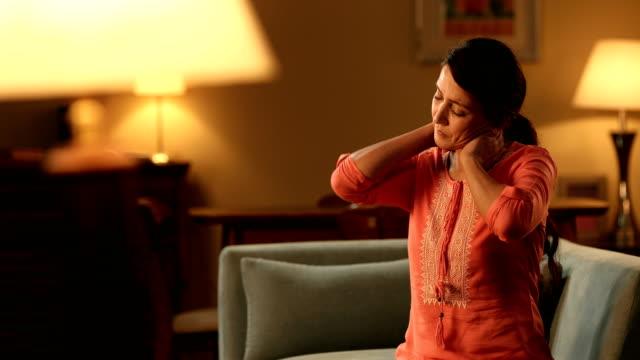 vídeos de stock e filmes b-roll de ms mature woman suffering from neck pain while sitting on sofa in living room/ delhi, india - dor no pescoço