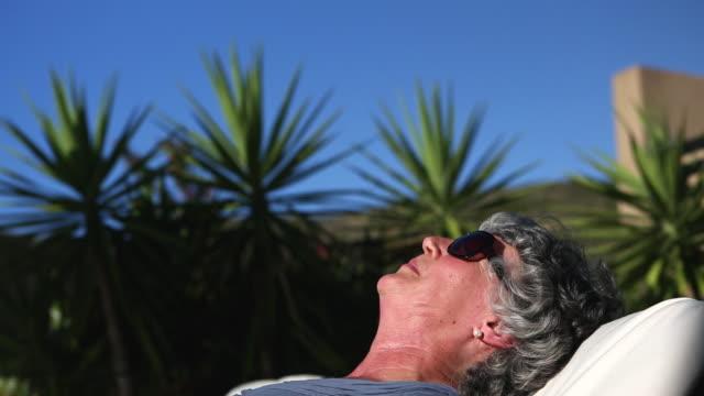 vídeos de stock, filmes e b-roll de mature woman sunbathing in a deckchair - cor de cabelo