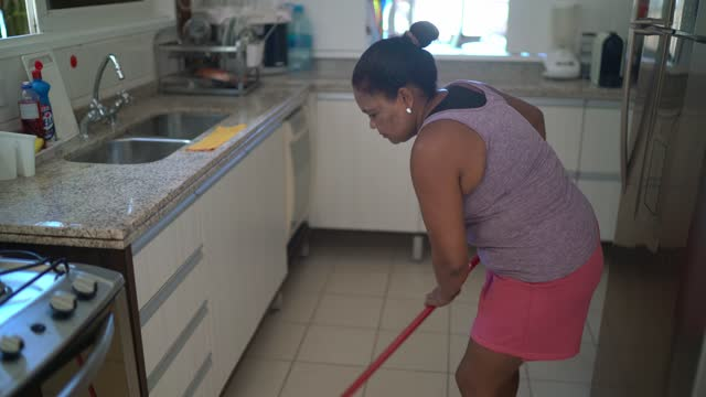 mature woman sweeping floor at home - sweeping stock videos & royalty-free footage