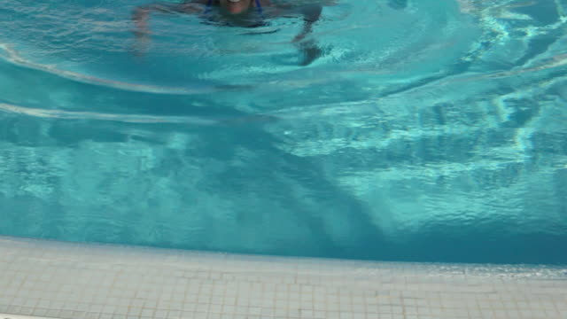 vídeos de stock e filmes b-roll de mature woman swimming in pool - one mature woman only