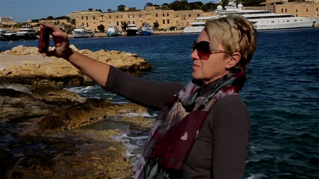 Mature woman takes selfie near the sea