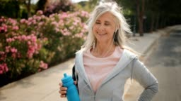 Mature woman taking a break from running outdoors and drinking water