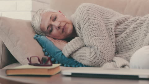 mature woman taking a nap on the sofa while resting at home. - sleeping stock videos & royalty-free footage