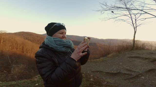 mature woman taking pictures of the nantahala national forest from cherohala skyway with a smartphone. fall cold evening. - appalachia stock videos & royalty-free footage