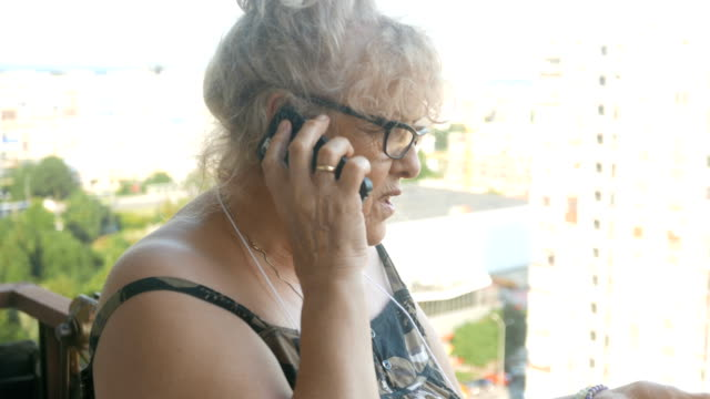 mature woman talking on the phone - reading glasses stock videos & royalty-free footage