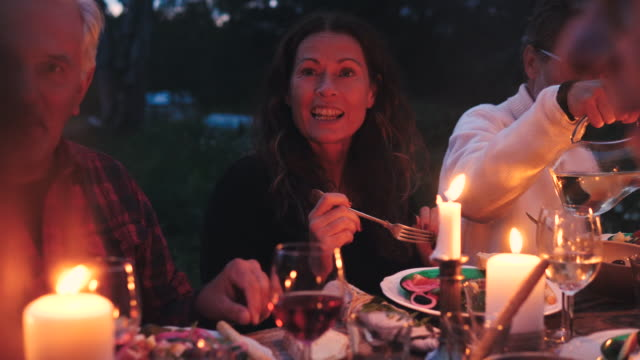 vidéos et rushes de mature woman talking to friends while eating meal during harvest dinner party at backyard at dusk - petit groupe de personnes