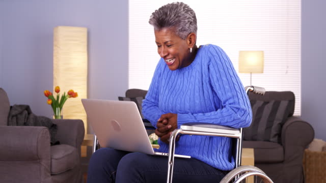 Mature woman talking with friend on laptop