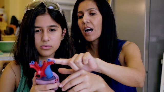vídeos de stock, filmes e b-roll de madura mulher ensinando preteen filha em casa de ciência classe de escola - biologia