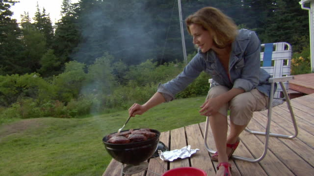 MS, SHAKY, Mature woman tending barbecue on porch, Vinal Haven, Maine, USA