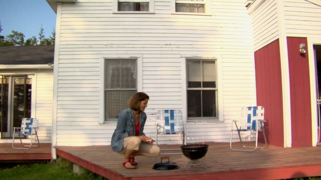 ws, mature woman tending barbecue on porch, vinal haven, maine, usa - しゃがむ点の映像素材/bロール