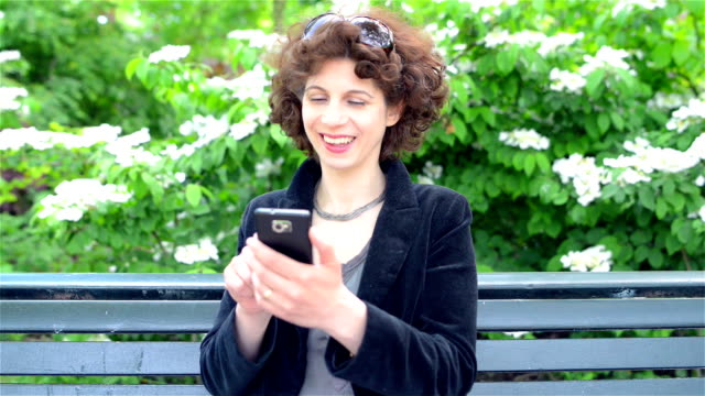 dolly: mature woman texting in a park - vondelpark stock videos and b-roll footage