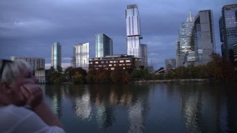 mogen kvinna, turist, ta bilder av austin downtown vid solnedgången från auditorium shores på town lake metropolitan park. hans, sverige - 45 49 år bildbanksvideor och videomaterial från bakom kulisserna