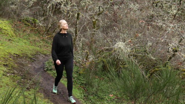 成熟した女性は冬に森の道を横断します - ウィンターコート点の映像素材/bロール