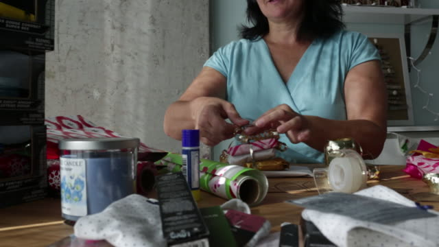ts ms mature woman tying ribbon on christmas gift. - wrapping paper stock videos & royalty-free footage