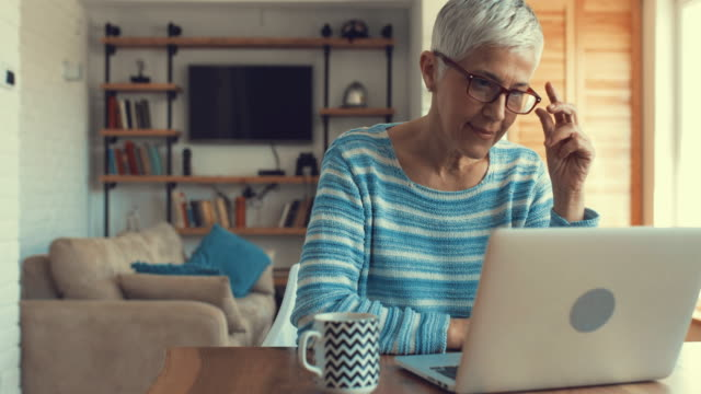 mature woman typing an e-mail on laptop at home. - one senior woman only stock videos & royalty-free footage
