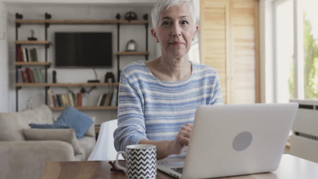 mature woman typing on laptop and showing thumb up towards the camera. - thumbs up stock videos & royalty-free footage