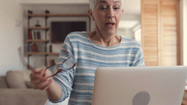 mature woman typing on laptop in the living room. - working from home stock videos and b-roll footage