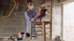 Mature Woman Upcycling Furniture In Workshop At Home Using Electric Sander