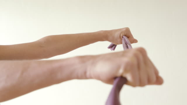 A mature woman uses a stretch band in her home gym.