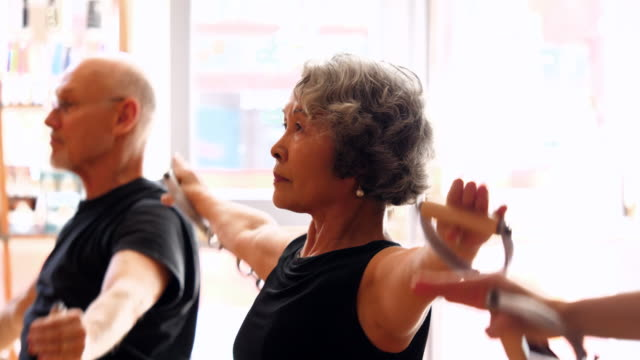 cu ts mature woman using arm straps on pilates reformer to exercise in fitness studio - aktiva pensionärer bildbanksvideor och videomaterial från bakom kulisserna