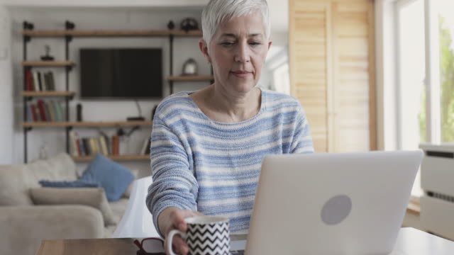 mature woman using computer and drinking coffee at home. - coffee drink stock videos & royalty-free footage